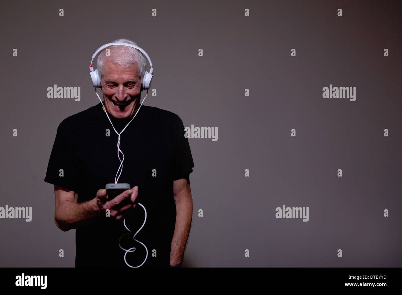 Portrait of senior man wearing headphones and using MP3 player - Stock Image