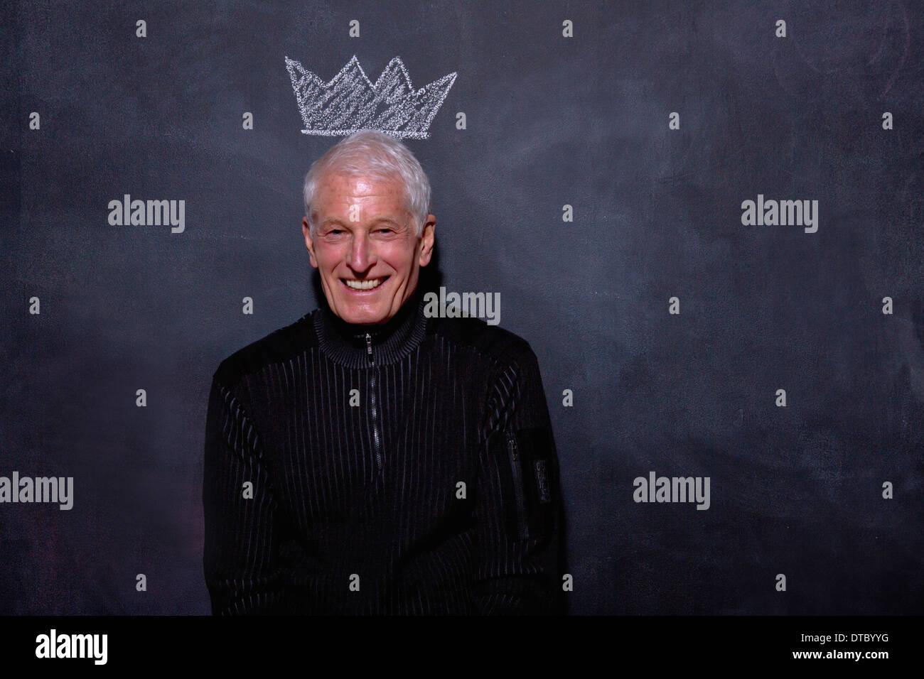 Portrait of senior man in front of chalked crown on blackboard - Stock Image