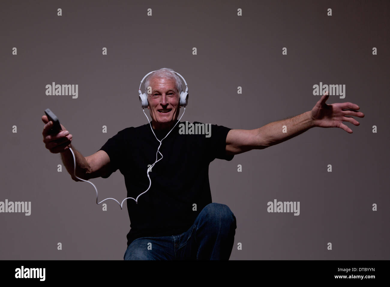 Portrait of senior man dancing to MP3 player on headphones - Stock Image