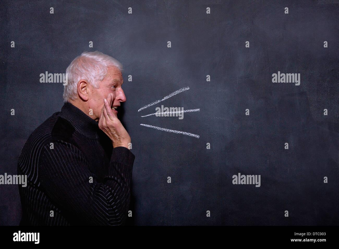 Portrait of senior man in front of blackboard - Stock Image