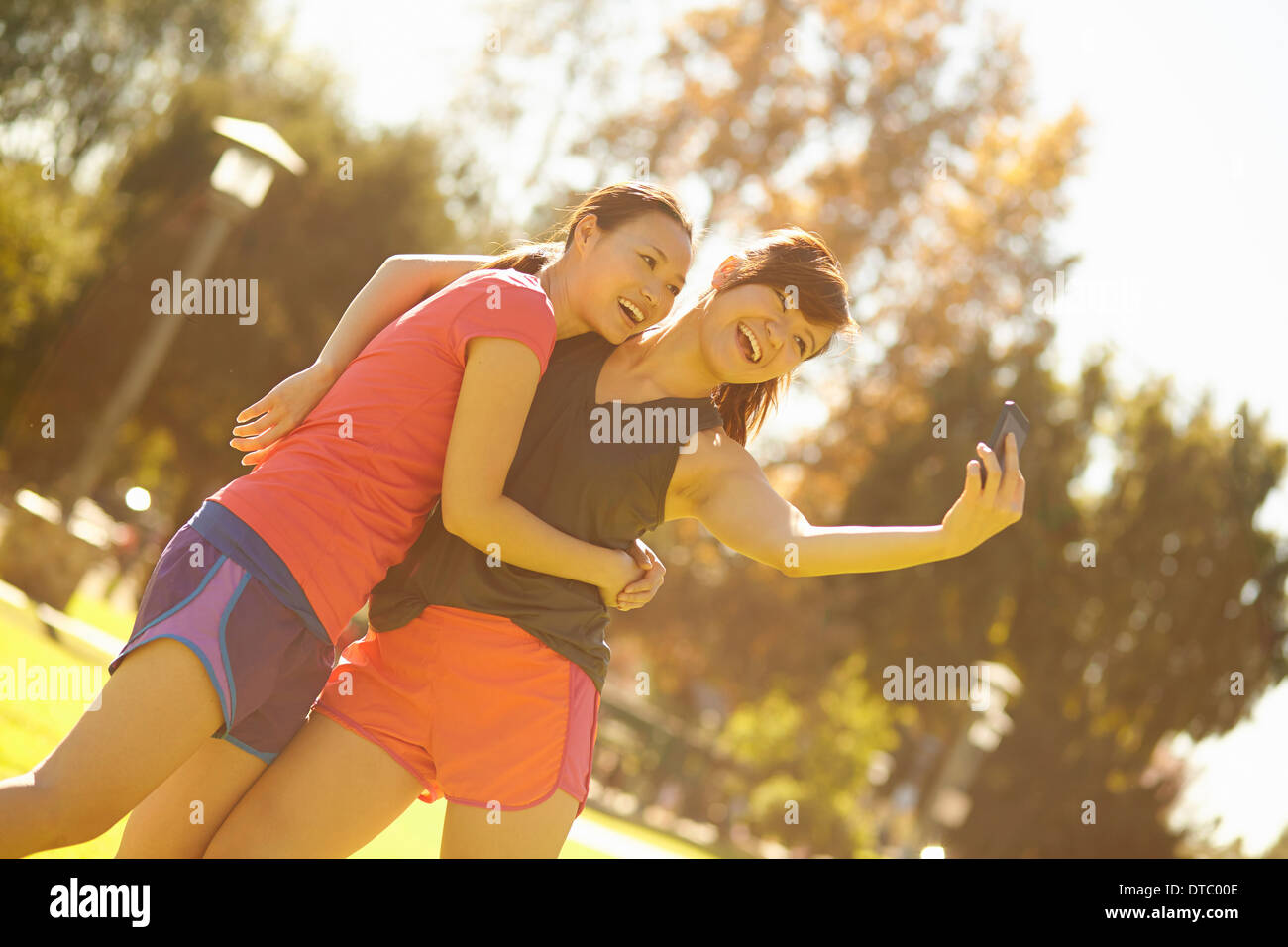 Two young women taking self portrait in park - Stock Image