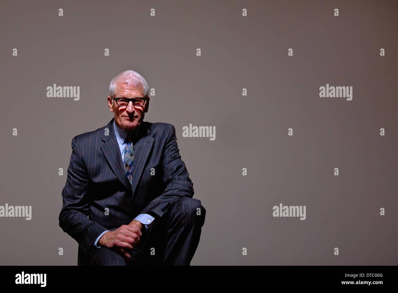 Studio portrait of cool senior man in suit - Stock Image