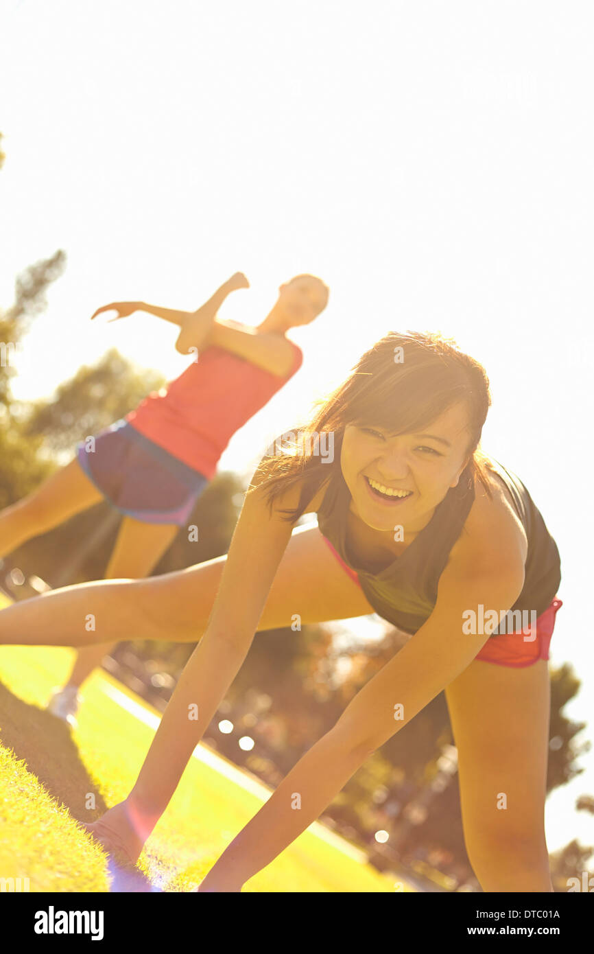 Two young women exercising in park - Stock Image