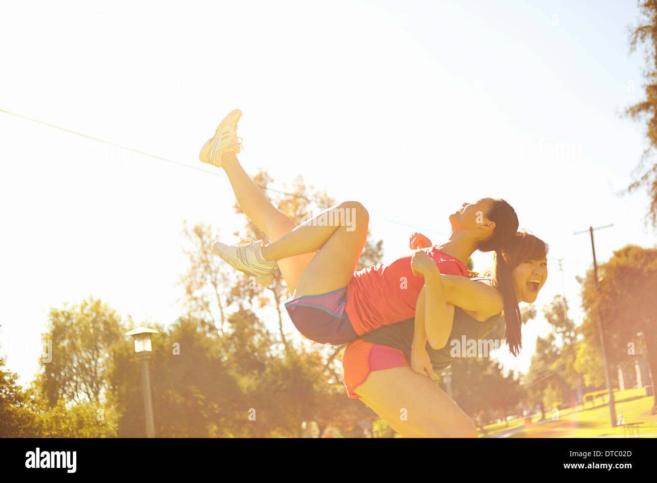 Two young women having fun in park - Stock Image