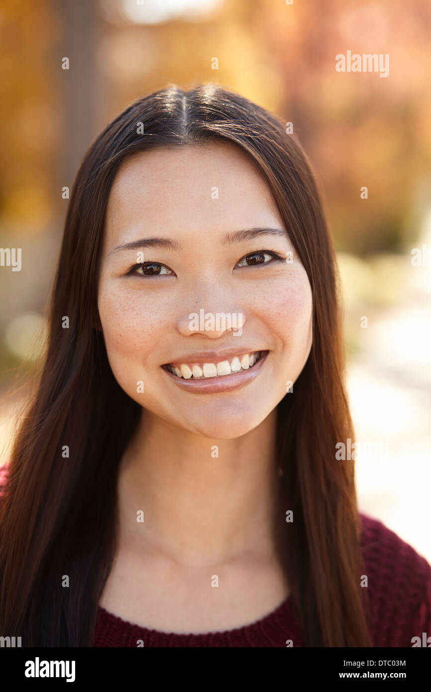 Portrait of young woman in park - Stock Image