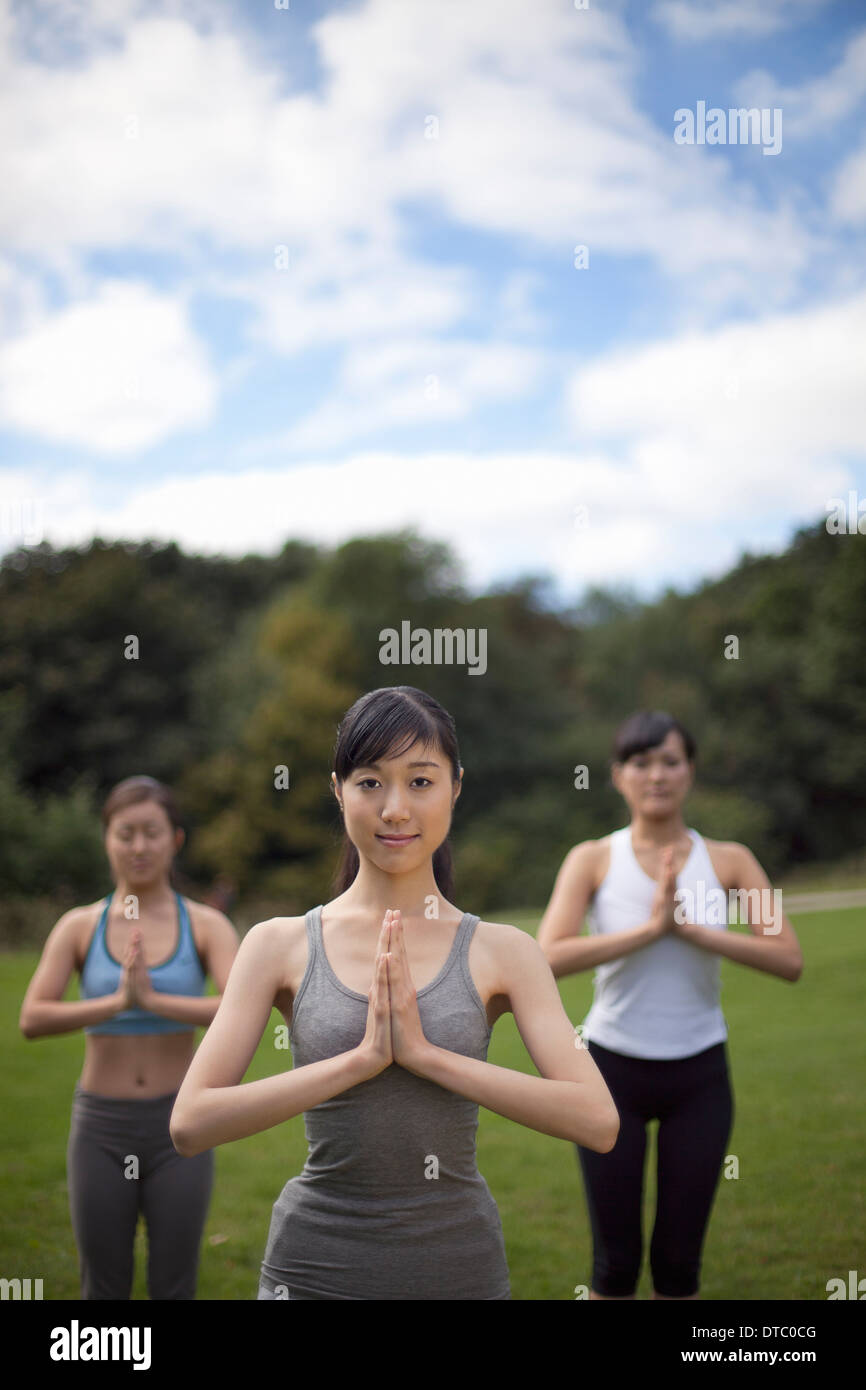 Three young women in park practicing yoga - Stock Image