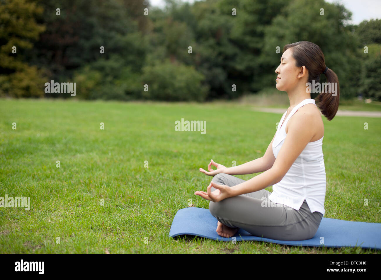 Young woman in park practicing yoga lotus position - Stock Image