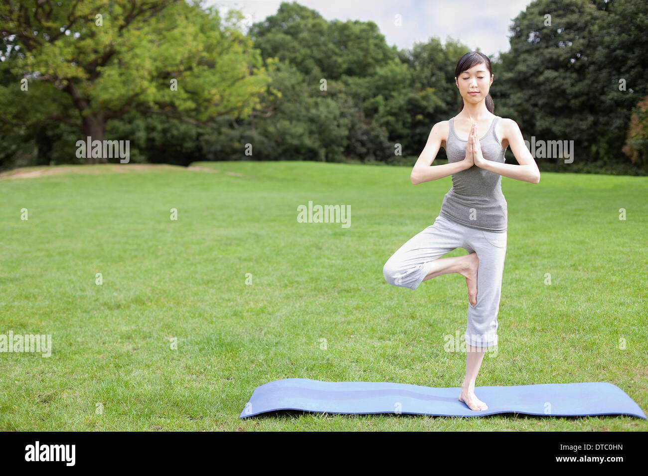 Young woman in park practicing yoga tree pose - Stock Image