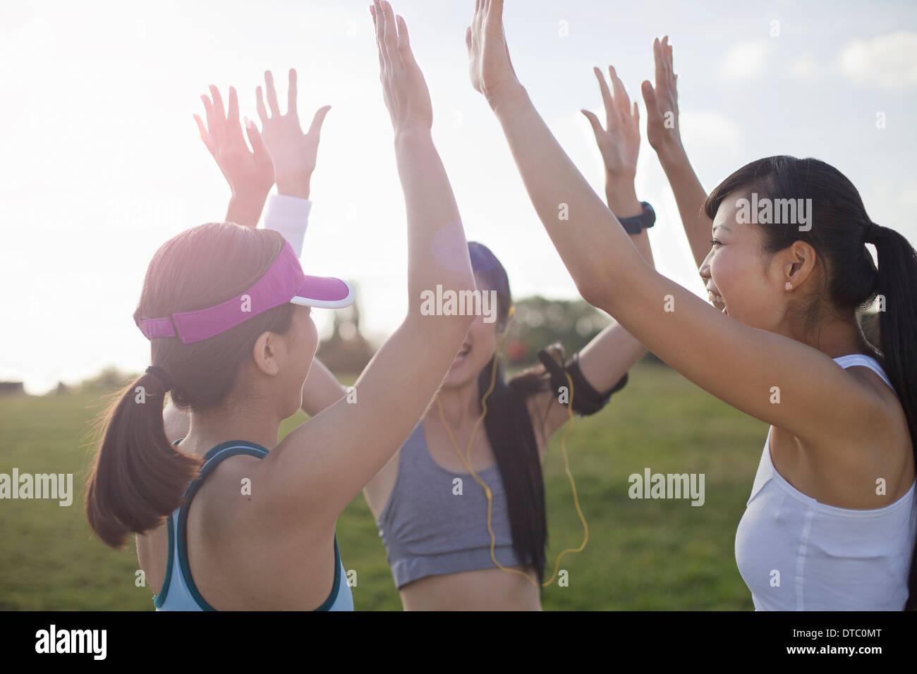Three young female runners preparing to run - Stock Image