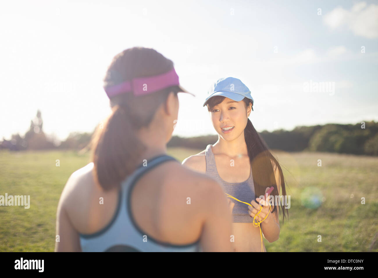 Two young female runners chatting - Stock Image