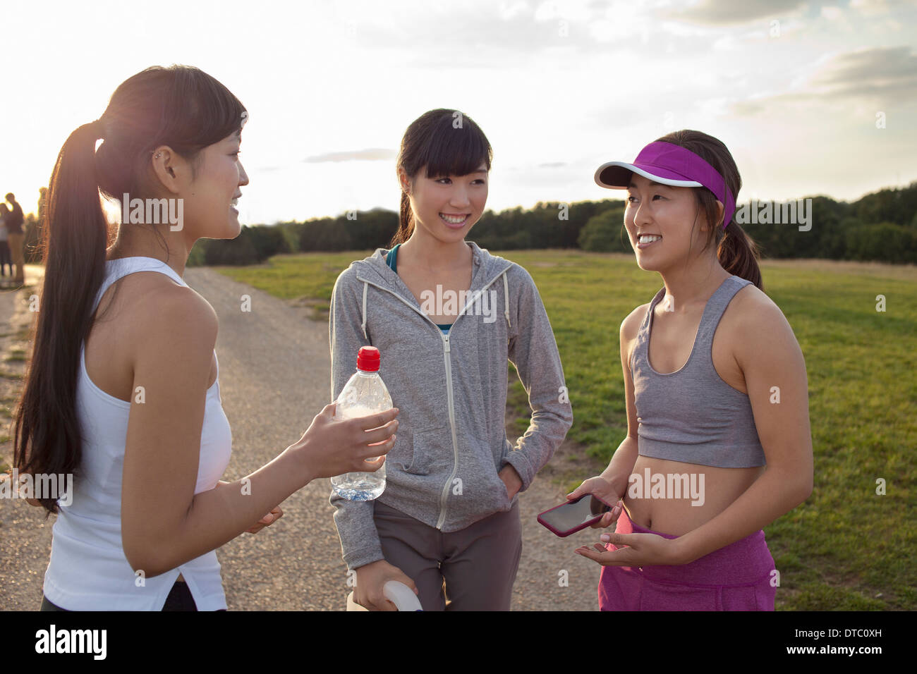 Three young female runners chatting after run - Stock Image