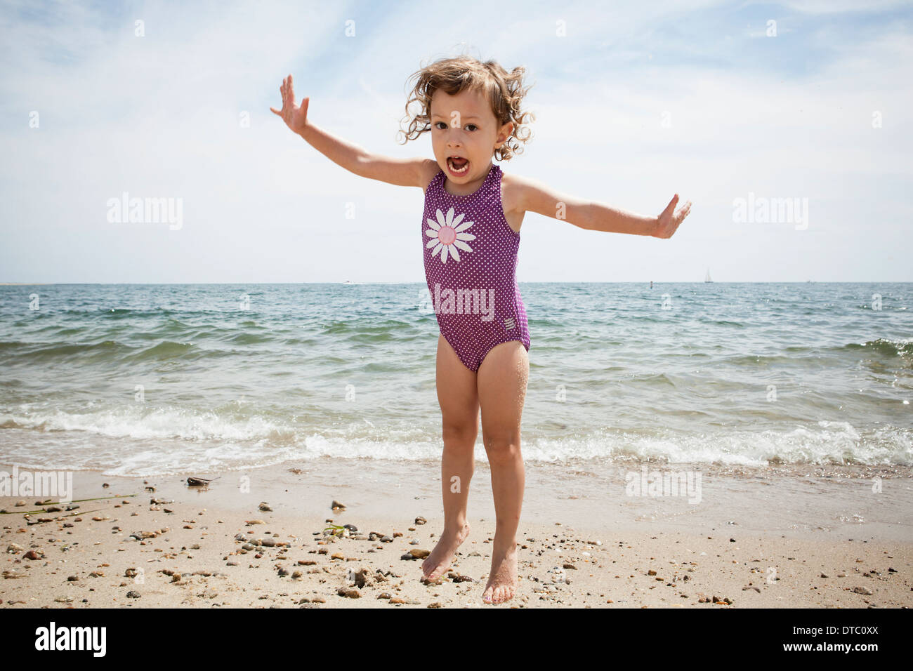 Portrait of jumping female toddler on beach at Falmouth, Massachusetts, USA - Stock Image