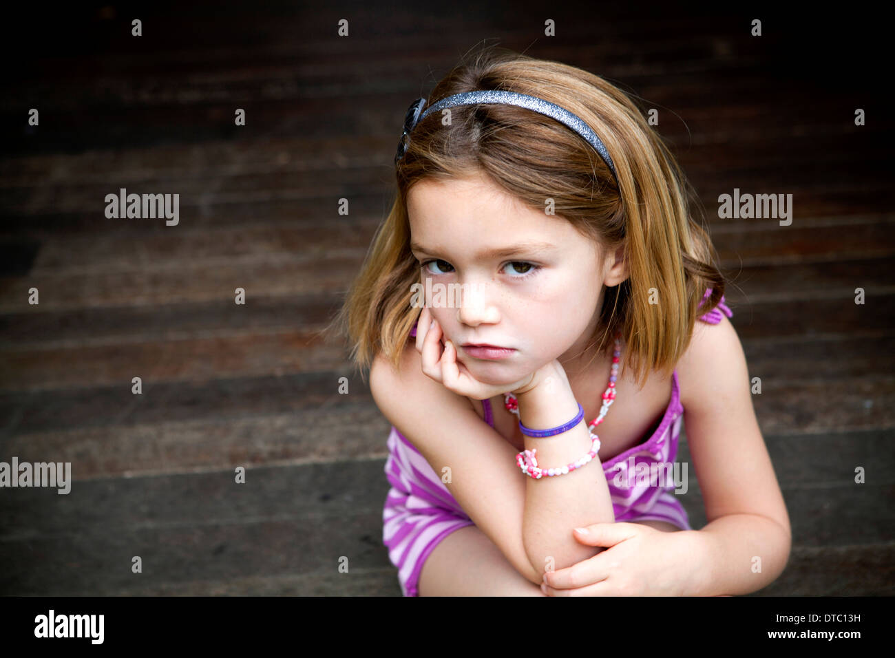 Sullen young girl sitting on porch with hands on chin - Stock Image