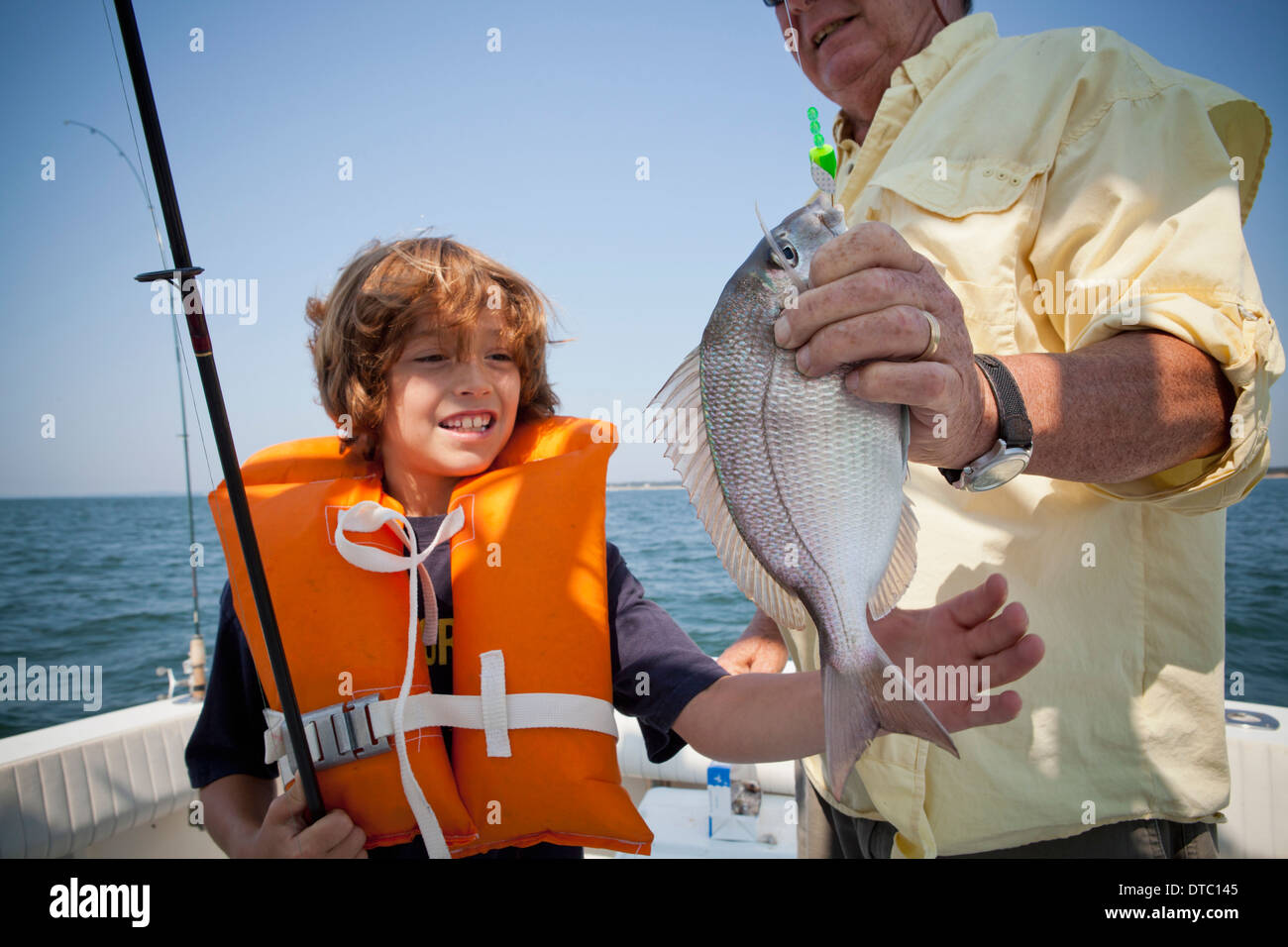 Boy and grandfather with caught fish on boat, Falmouth, Massachusetts, USA - Stock Image