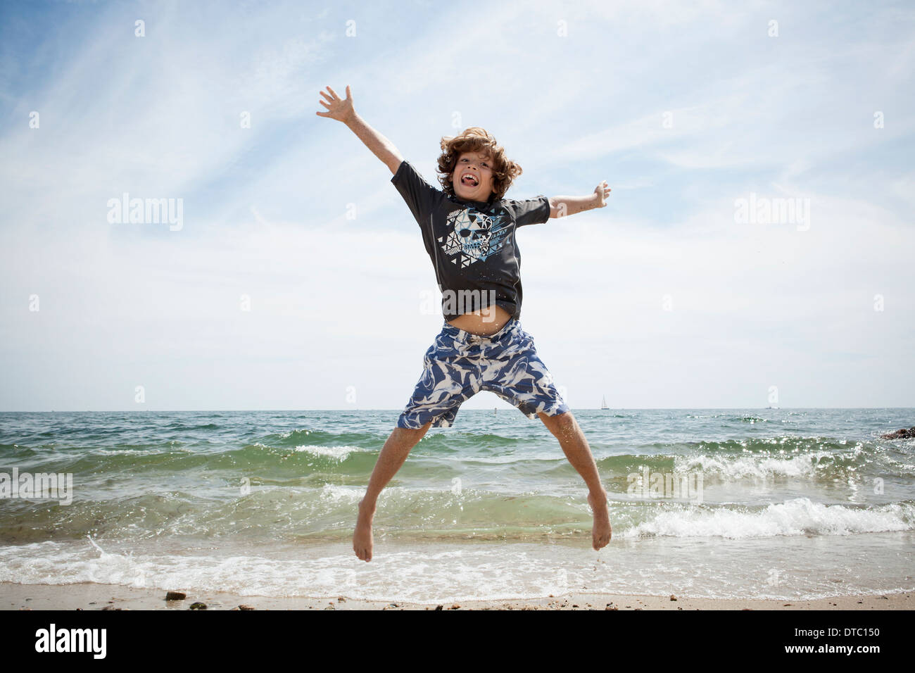 Informal portrait of jumping boy on beach at Falmouth, Massachusetts, USA - Stock Image