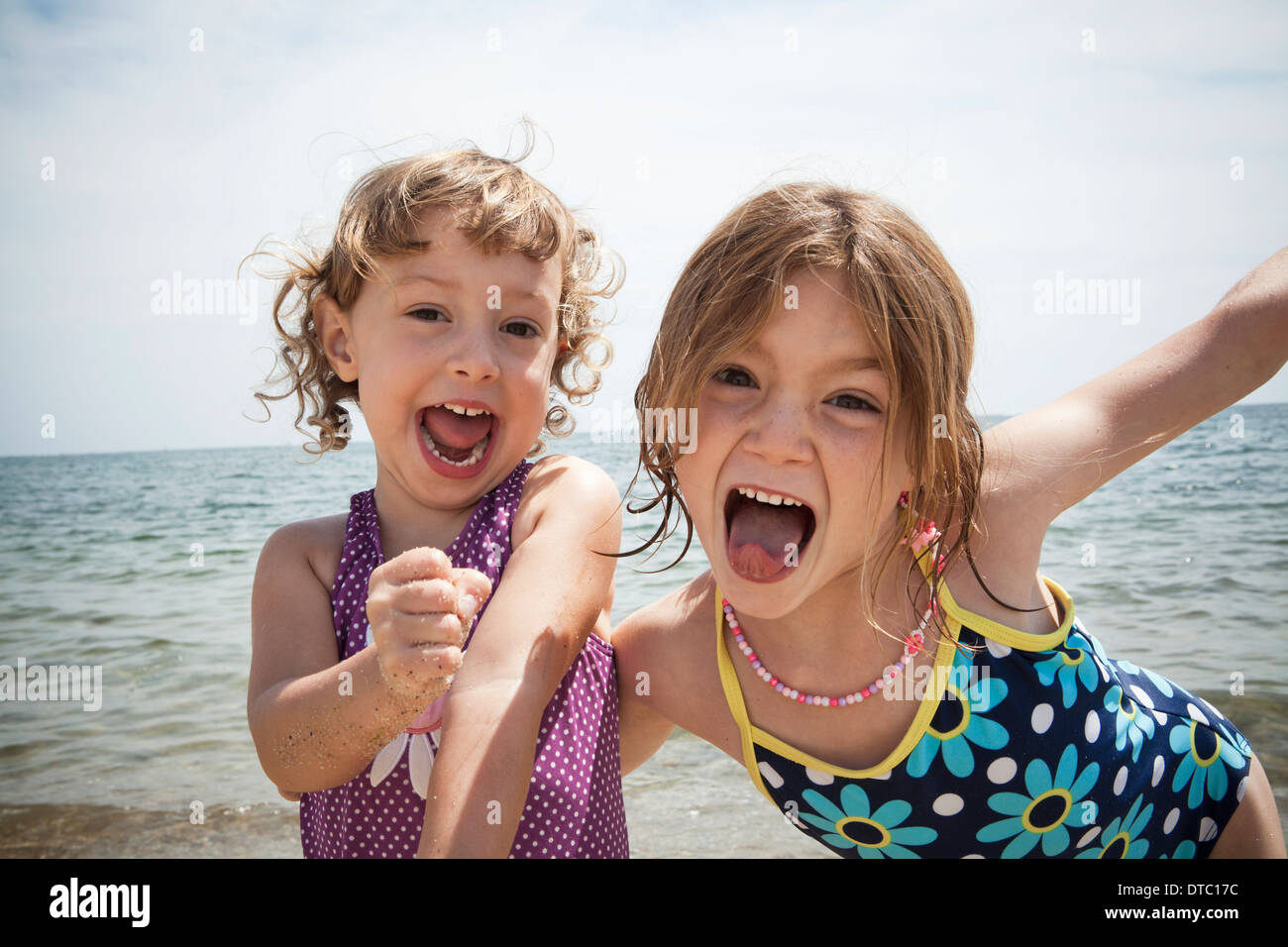 Portrait of two sisters pulling faces on beach at Falmouth, Massachusetts, USA - Stock Image