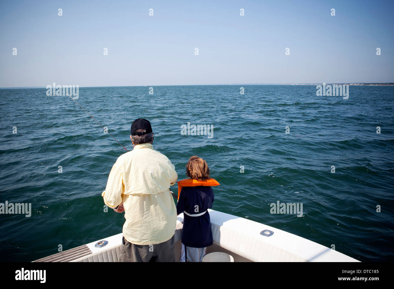 Boy and grandfather fishing from boat, Falmouth, Massachusetts, USA - Stock Image