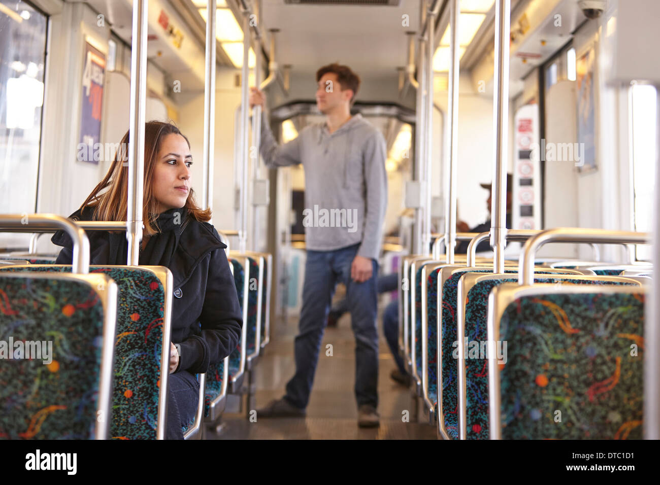 Commuters on empty subway train - Stock Image
