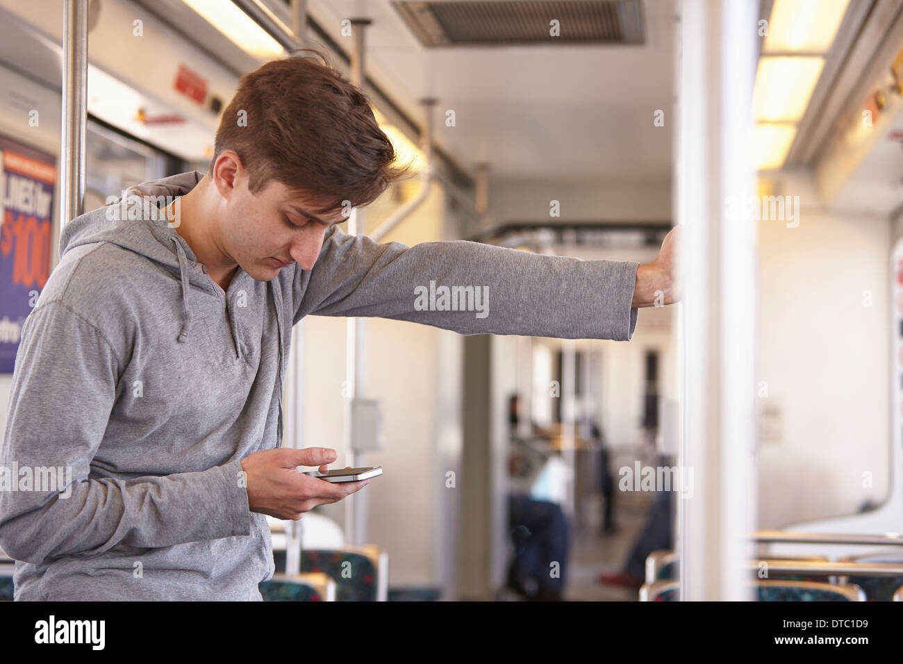 Mid adult man using cellphone on subway train - Stock Image