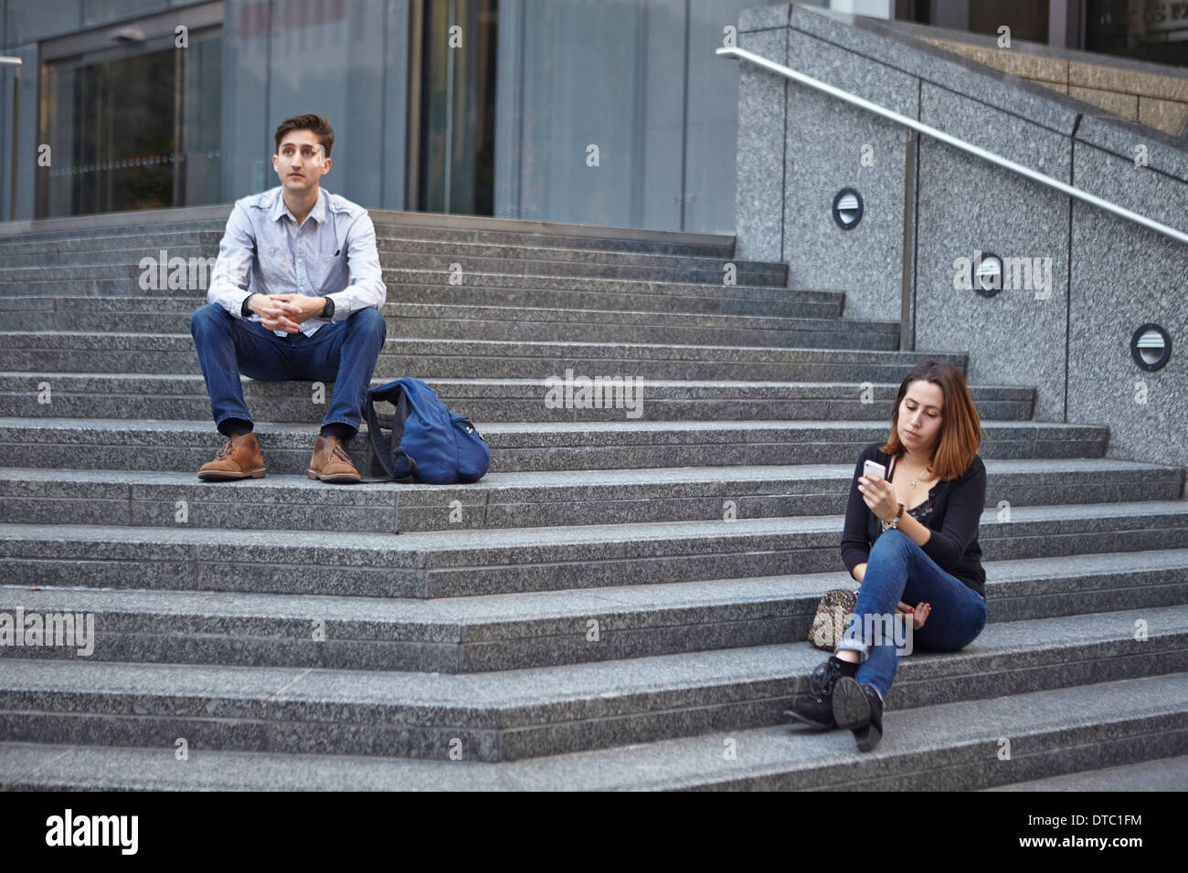 Unhappy couple sitting apart on steps - Stock Image