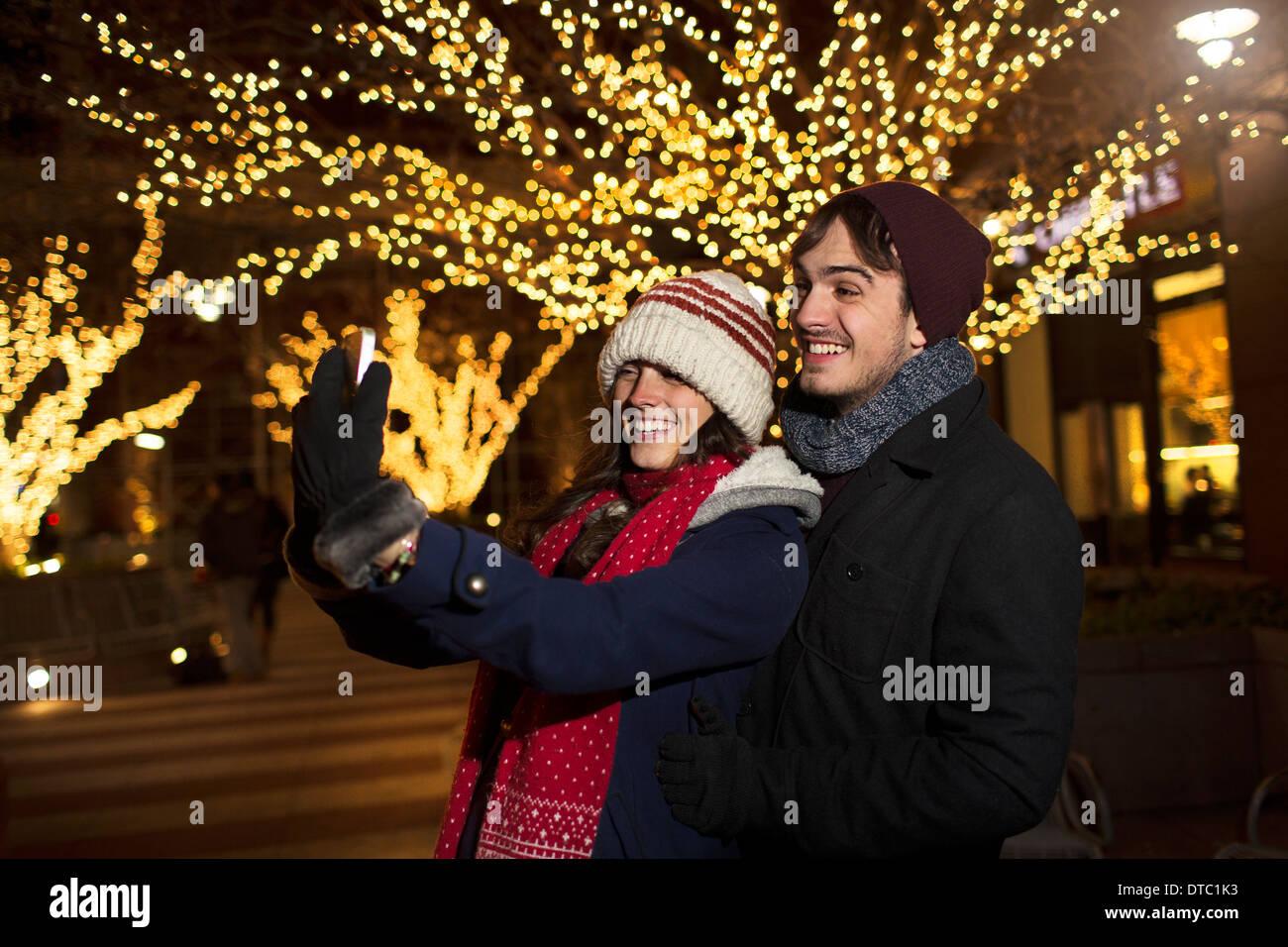Young couple enjoying christmas celebrations on street - Stock Image