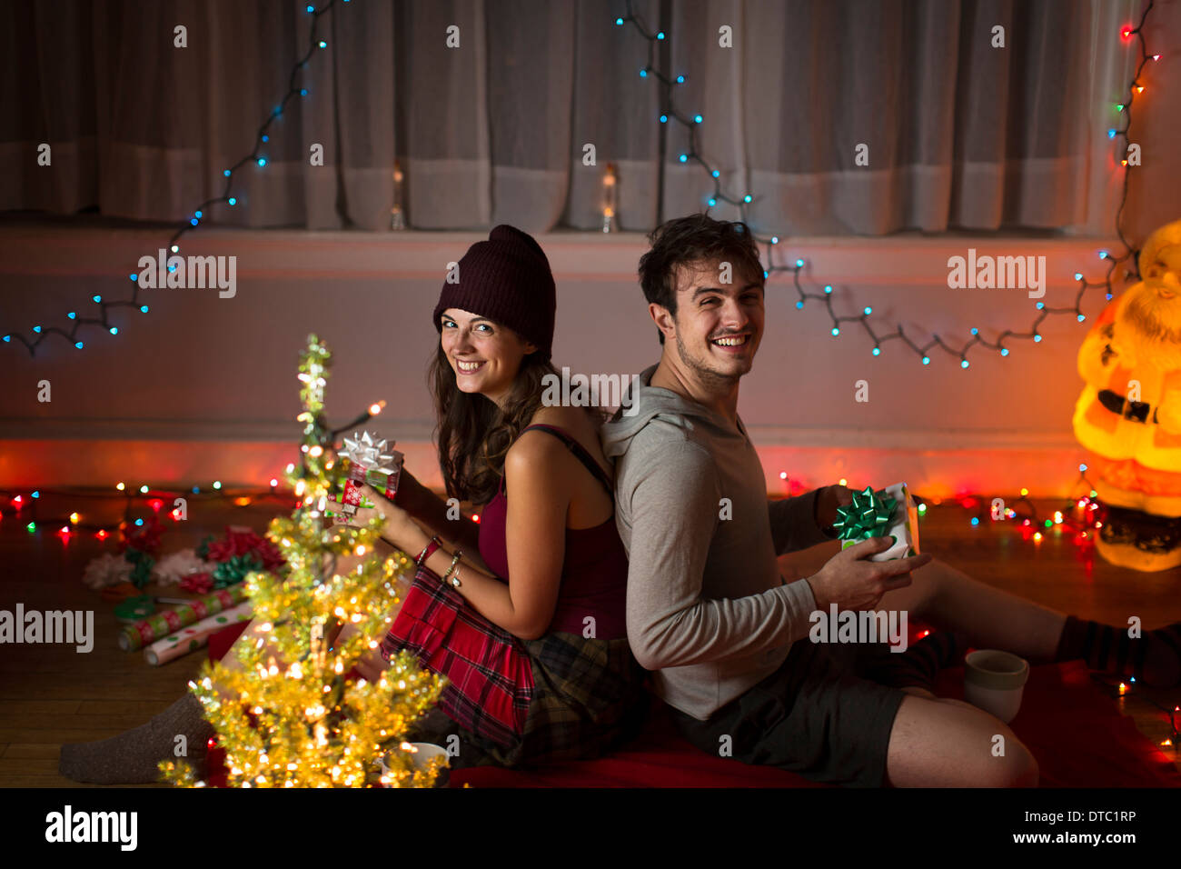 Young couple exchanging gifts in sitting room at christmas - Stock Image