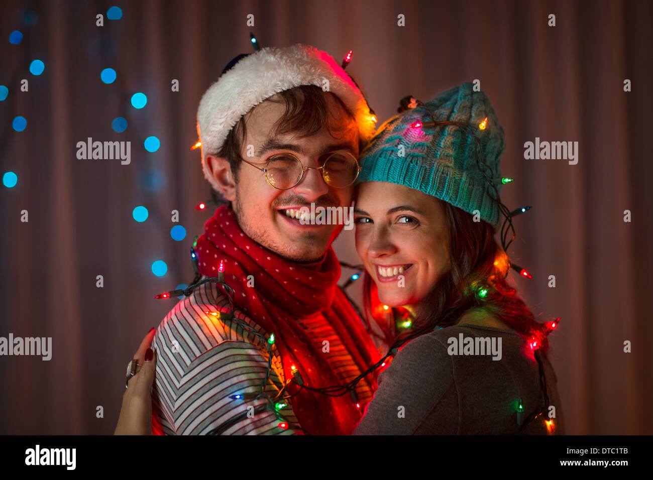 Young couple wrapped in decorative lights at christmas Stock Photo