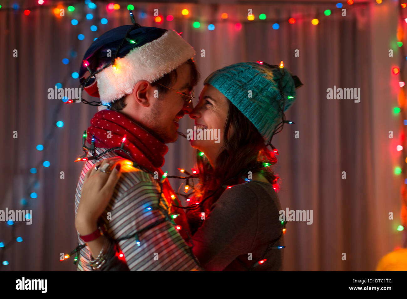 Romantic young couple wrapped in decorative lights at christmas Stock Photo