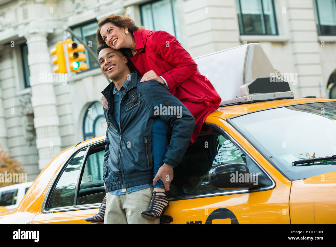 Young tourist couple with yellow cab, New York City, USA - Stock Image