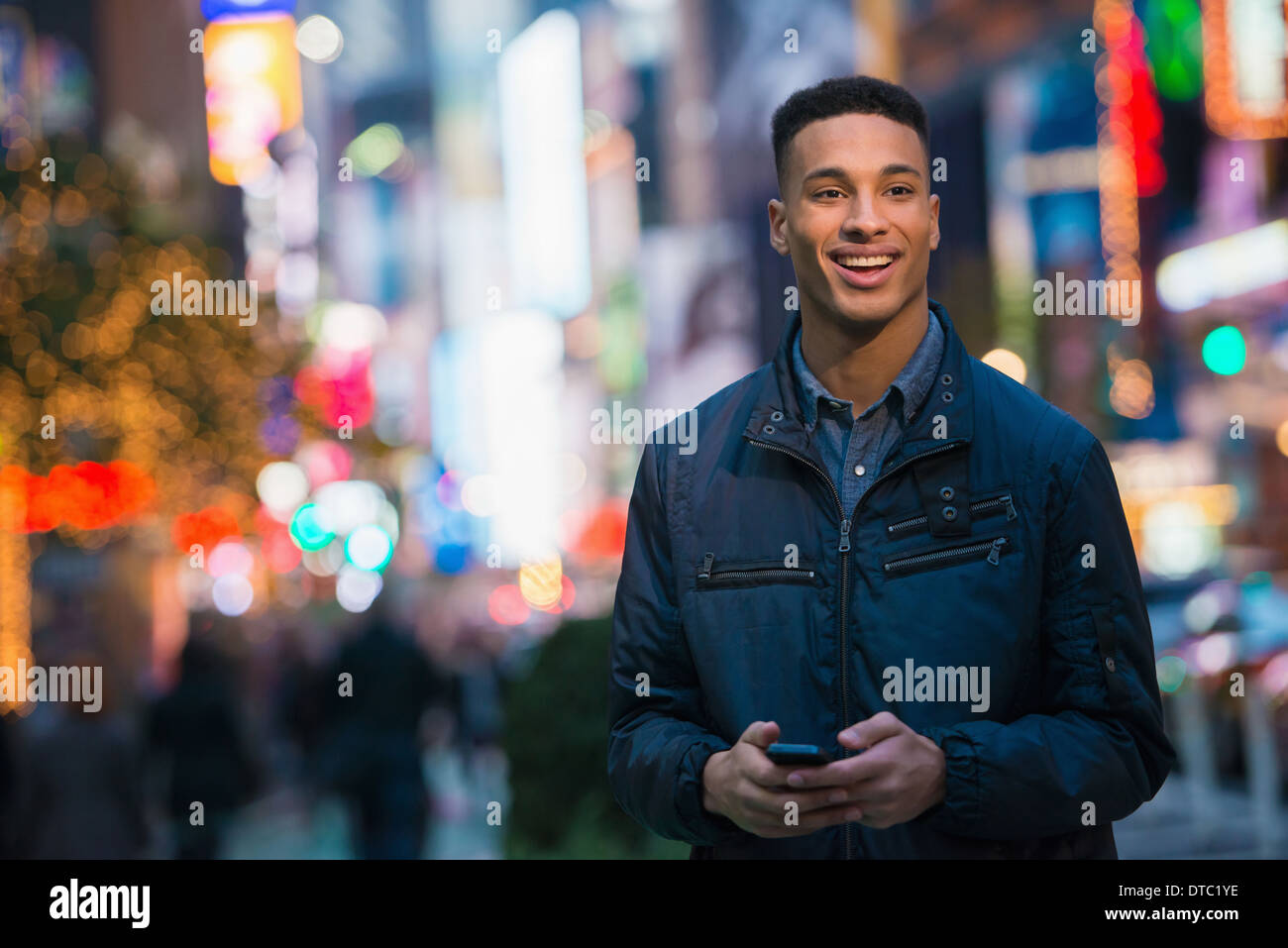 Young male tourist on busy street, New York City, USA - Stock Image