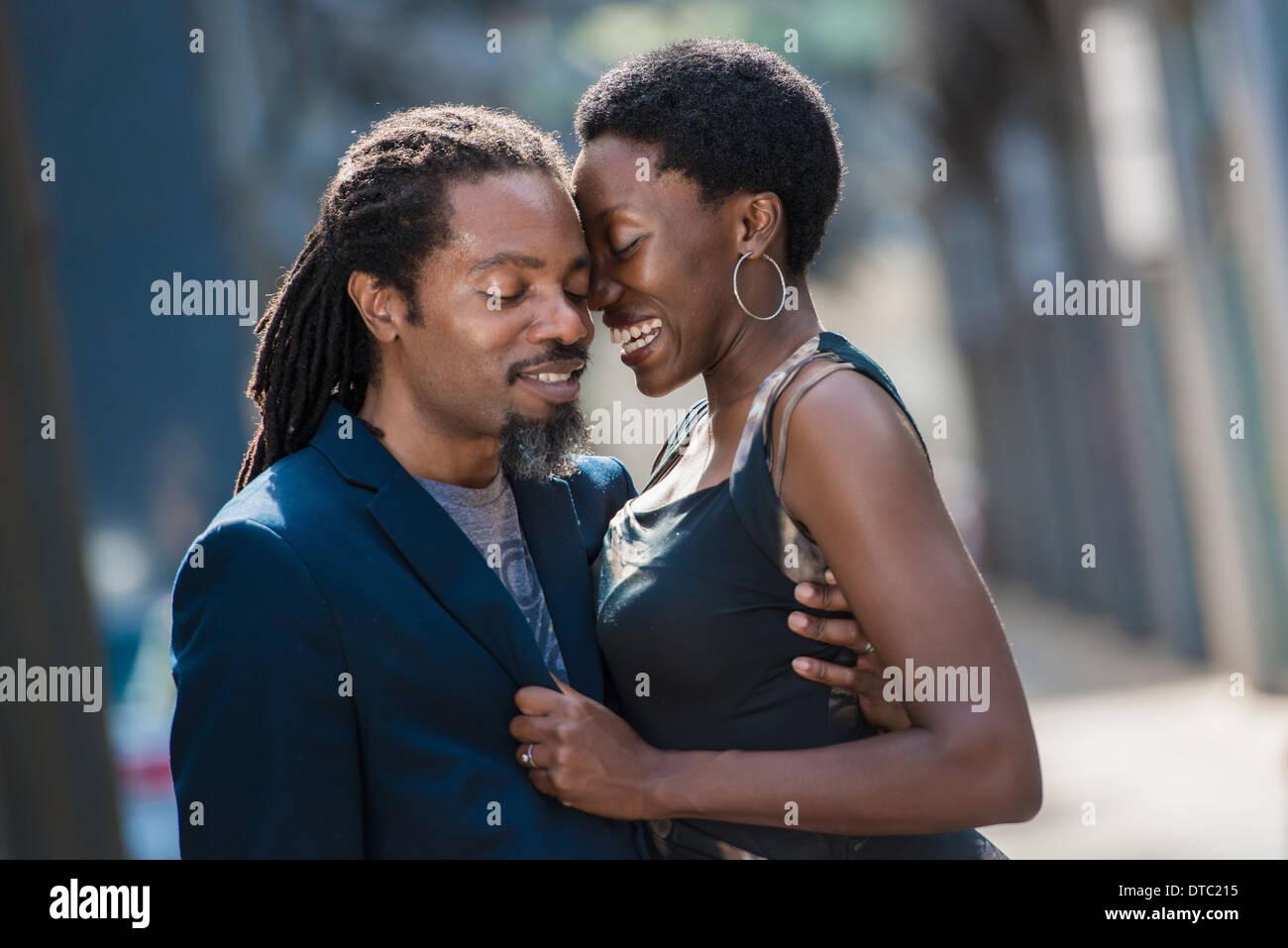 Couple embracing on street Stock Photo