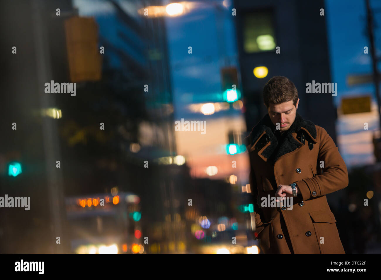Young man waiting on street looking at watch, Toronto, Ontario, Canada - Stock Image