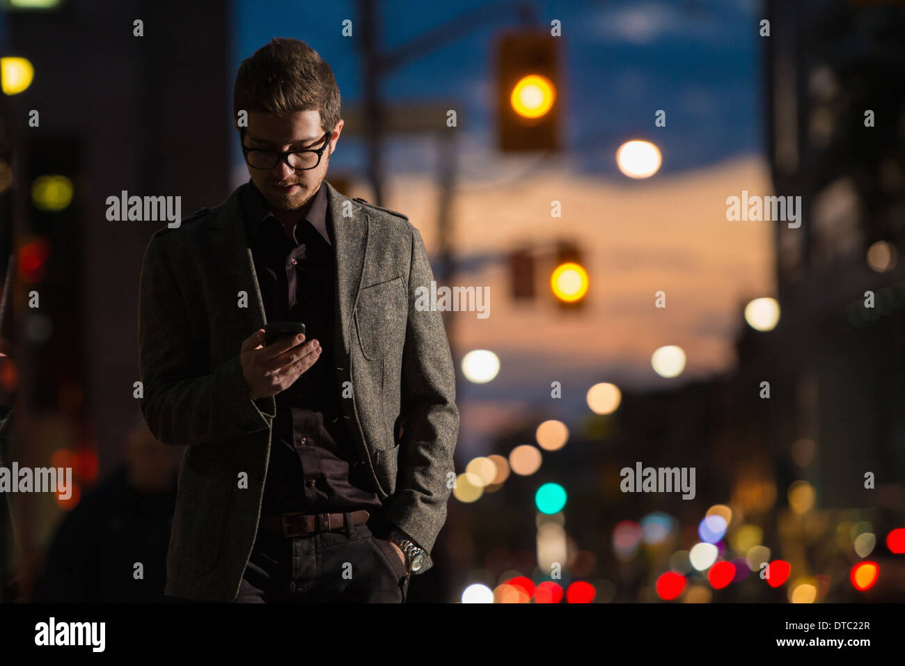 Young man strolling down street looking at mobile phone, Toronto, Ontario, Canada - Stock Image