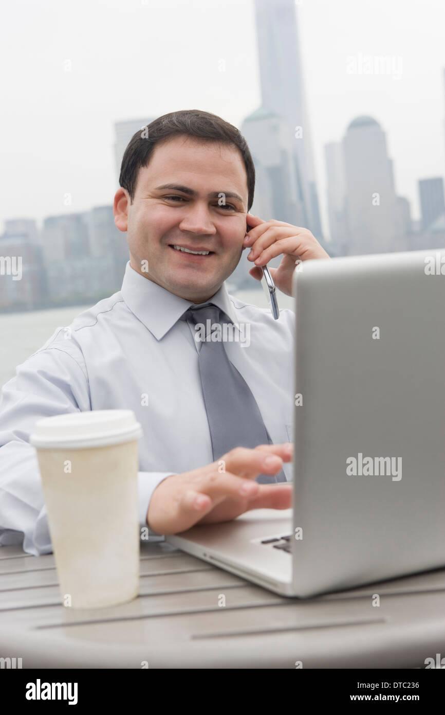Businessman using laptop outdoors, Jersey City, New Jersey, USA - Stock Image