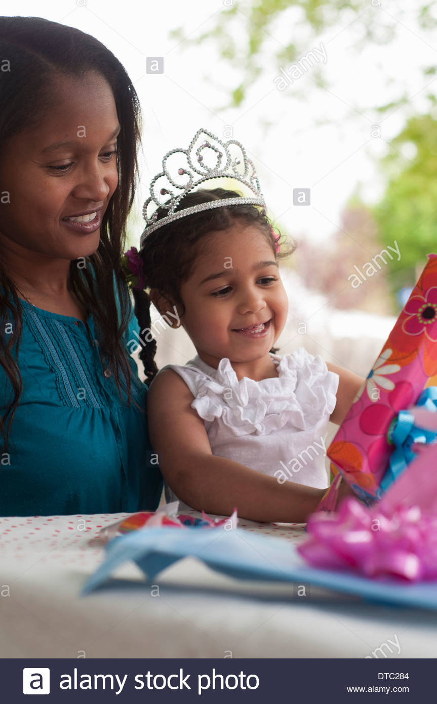 Mother with birthday girl opening presents - Stock Image