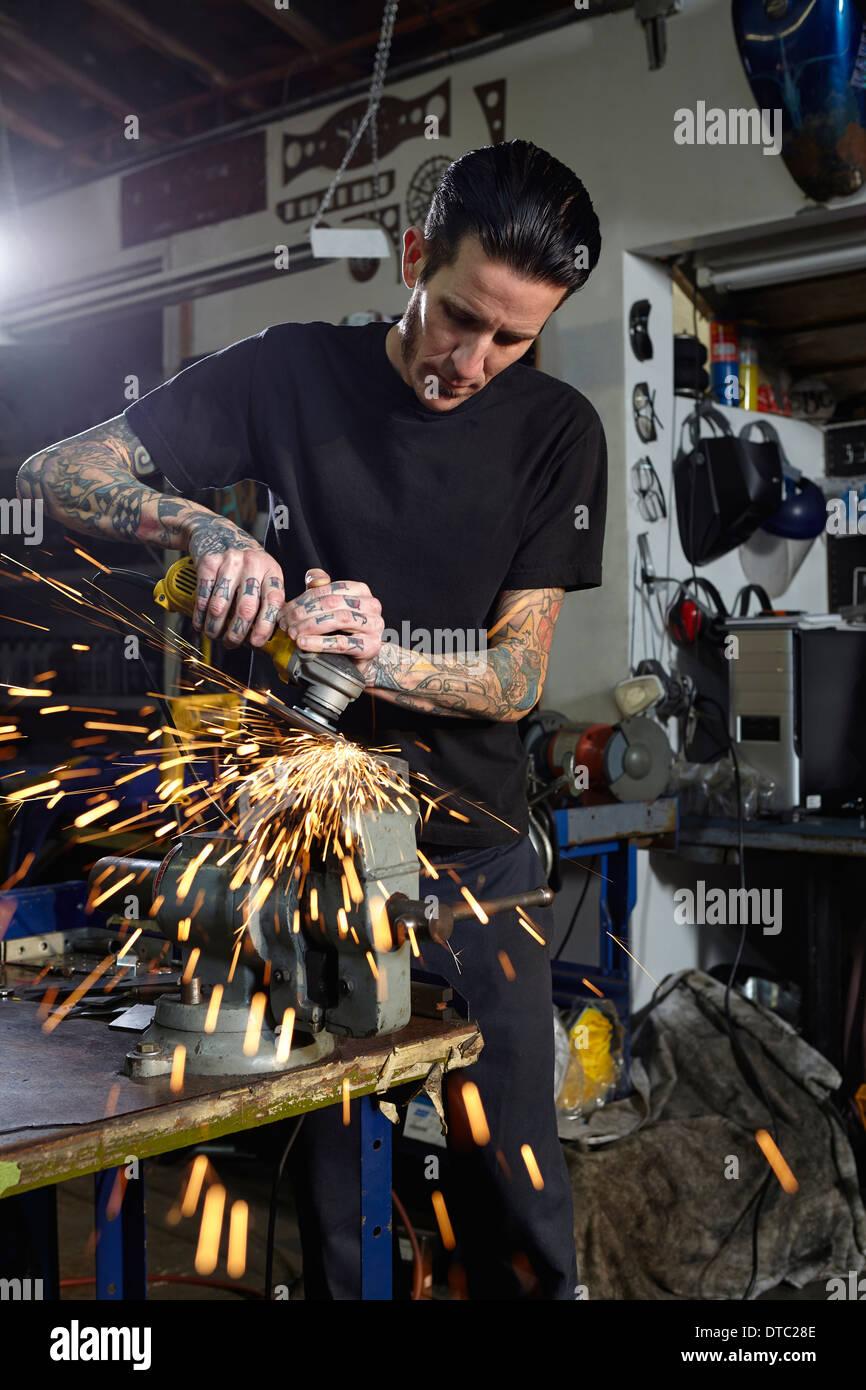 Mature man welding parts in motorcycle repair workshop - Stock Image