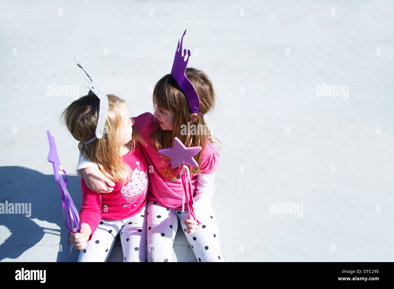 Two young sisters dressed up as fairies holding wands - Stock Image