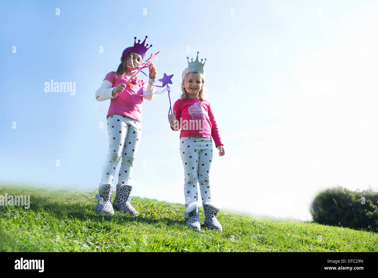 Two young sisters dressed up as fairies standing on hill - Stock Image
