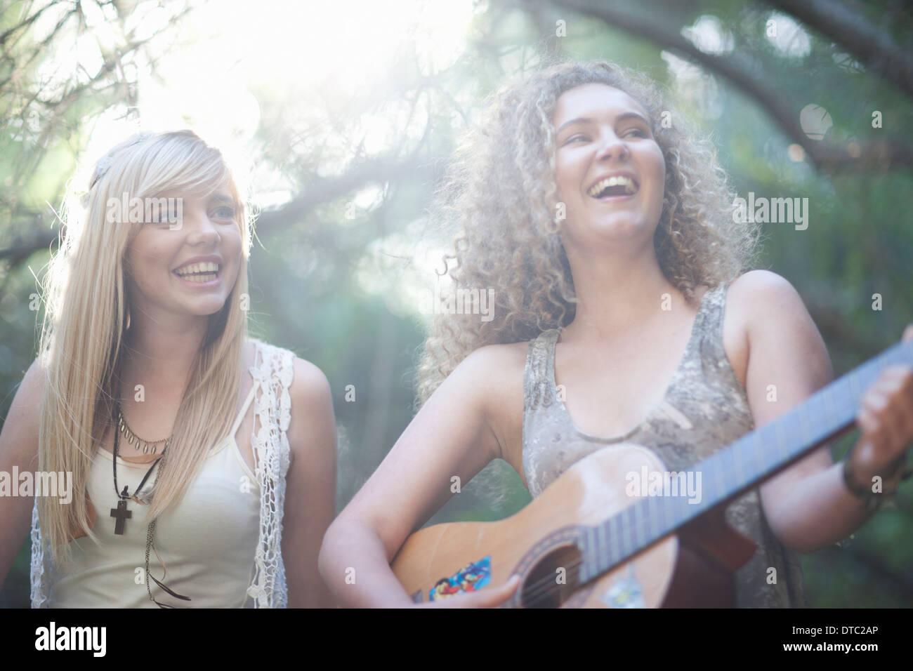Two teenage girls playing guitar in woodland - Stock Image
