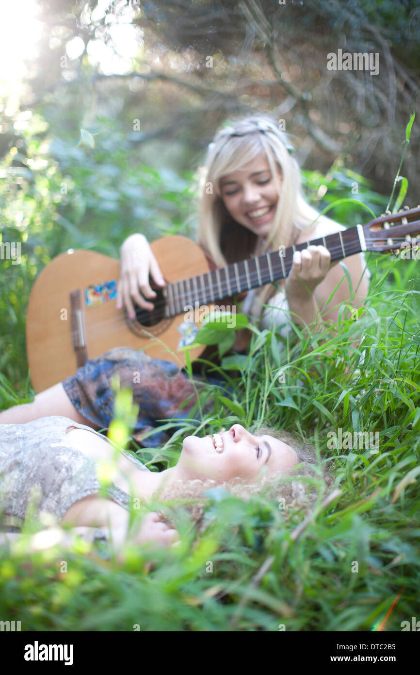 Two teenage girls listening to guitar in woodland - Stock Image