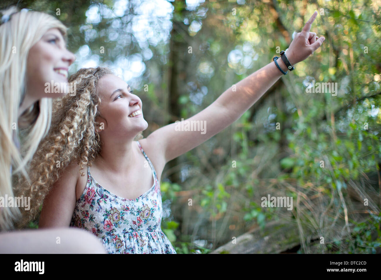 Two teenage girls exploring in woodland - Stock Image