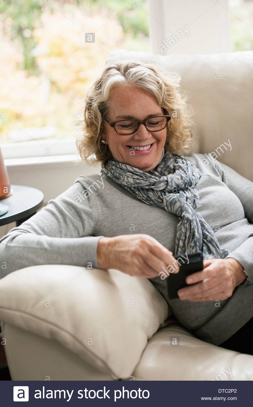 Relaxed senior woman sitting on sofa using mobile phone - Stock Image