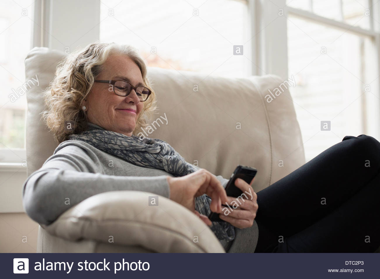 Senior woman relaxing on chair with mobile phone - Stock Image