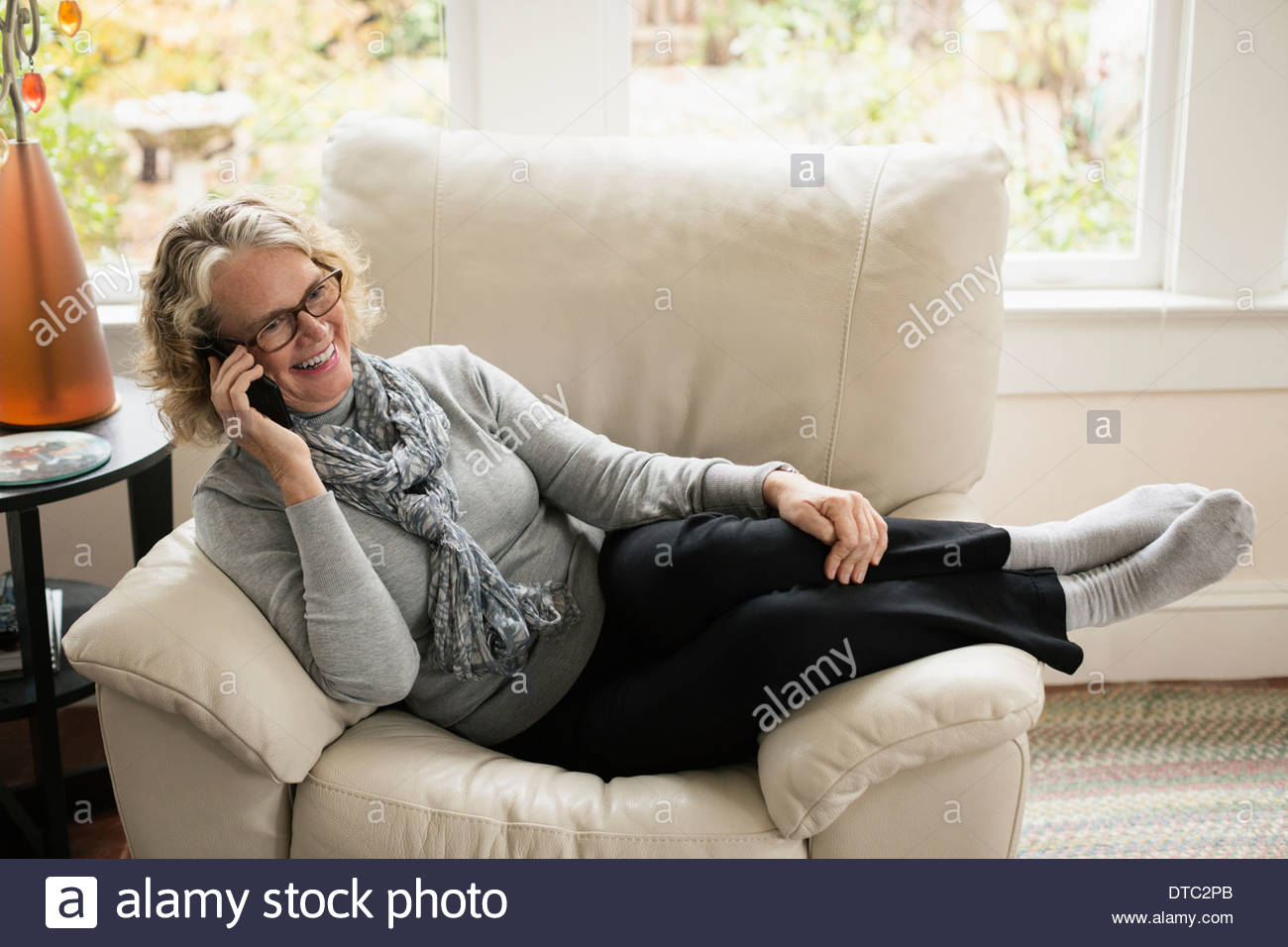 Relaxed senior woman sitting on chair talking on mobile - Stock Image