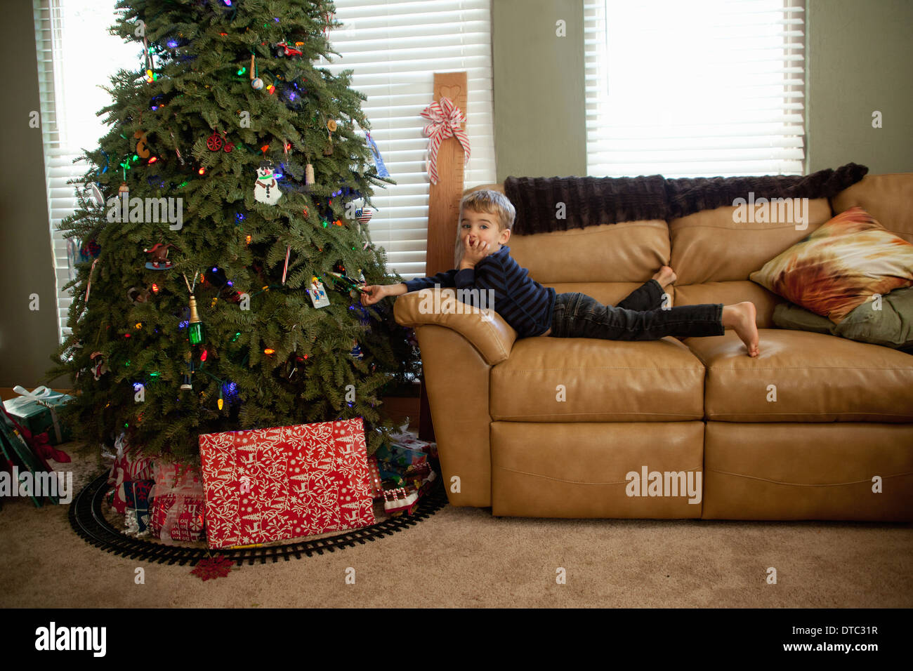 Excited male toddler looking at decorations on xmas tree - Stock Image