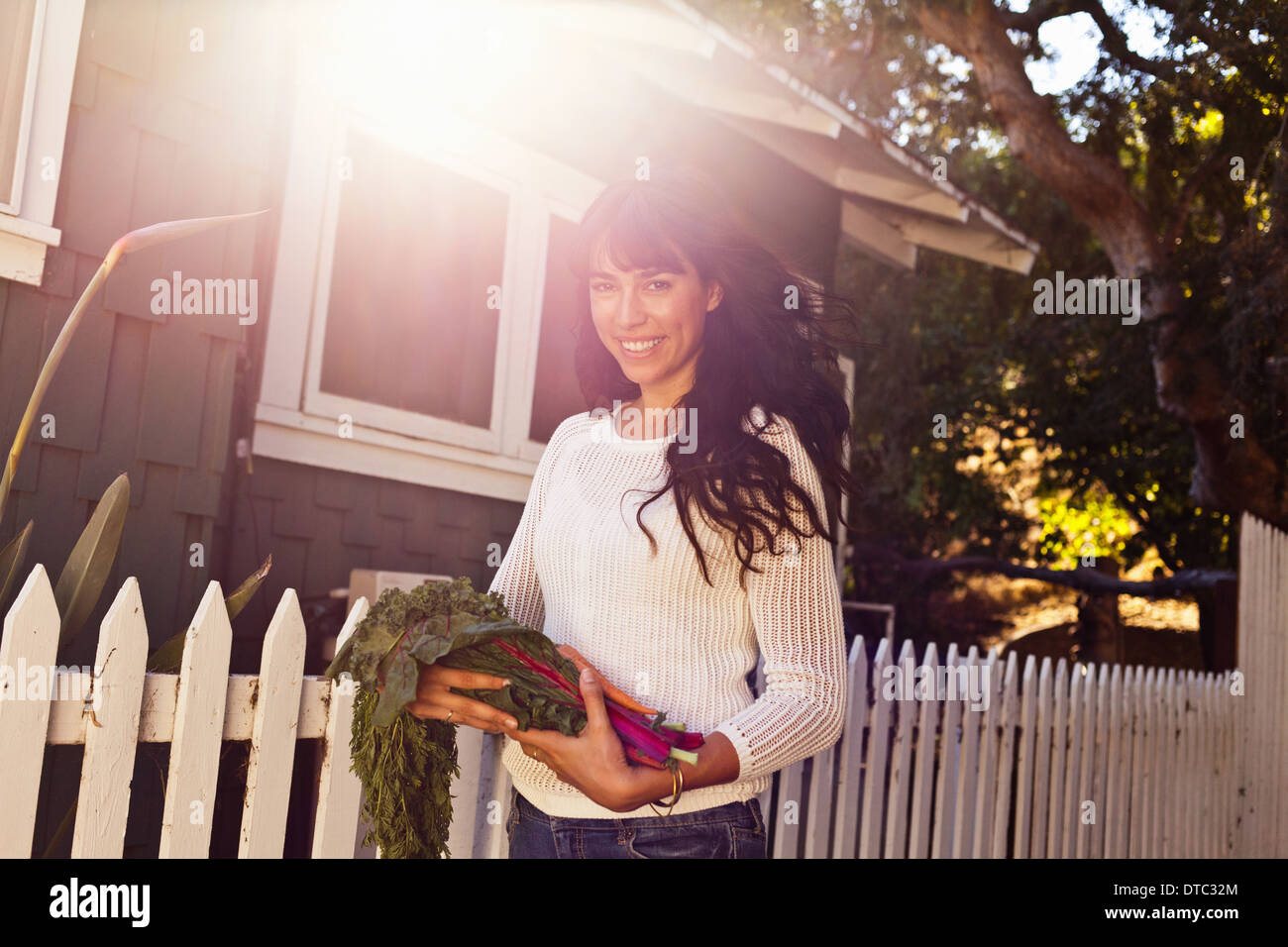 Portrait of young woman holding homegrown vegetables - Stock Image