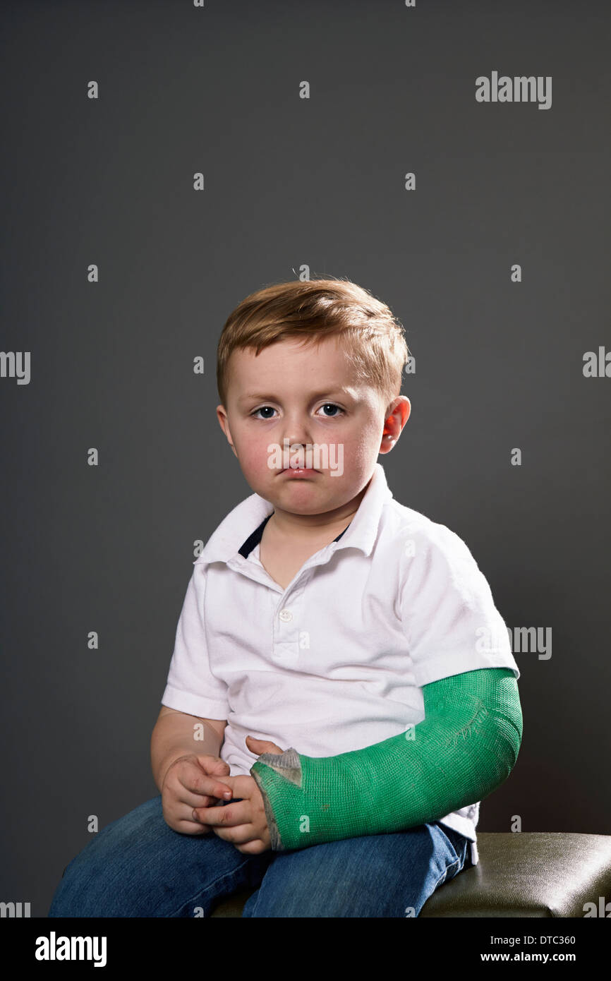 Portrait of sullen young boy with plaster cast on arm - Stock Image