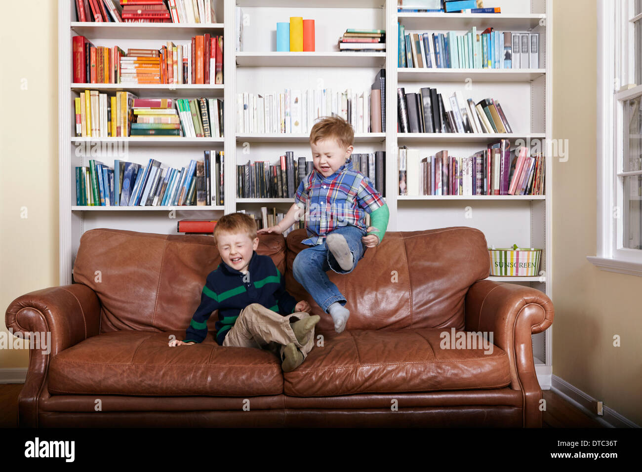 Two young brothers jumping on sofa - Stock Image