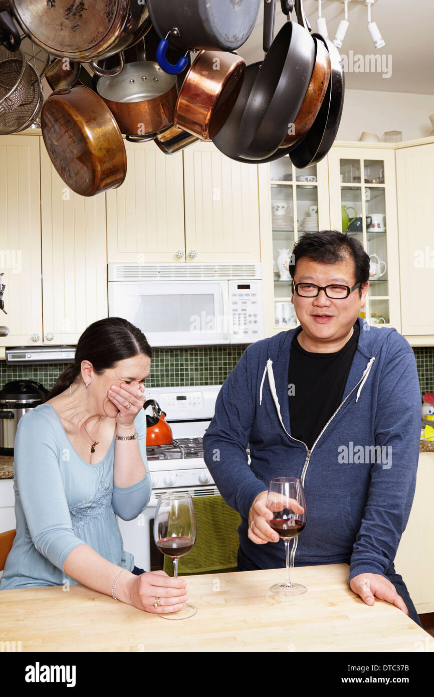 Mature couple relaxing with a glass of wine in kitchen - Stock Image