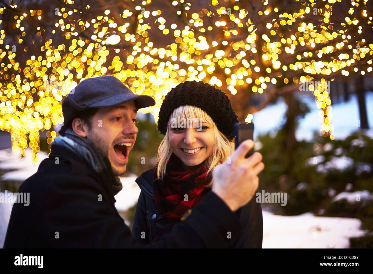 Young couple taking self portrait with outdoor xmas lights - Stock Image